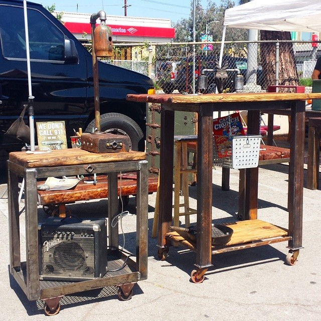 The vendor in B22 showcases his reclaimed industrial  furniture pieces next to artwork he purchased at #MTPfairfax.